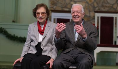 """Former President Jimmy Carter, right, sits with his wife, Rosalynn, as they wait to pose for photos with guests at Maranatha Baptist Church,  Sunday, Dec. 13, 2015, in Plains, Ga.  A recent MRI showing no cancer on Jimmy Carter's brain is """"very positive"""" news for the former president but will not end his medical treatment, doctors said. Carter, 91, announced last Sunday that doctors found no evidence of the four lesions discovered on his brain this summer and no signs of new cancer growth.  (AP Photo/Branden Camp)"""