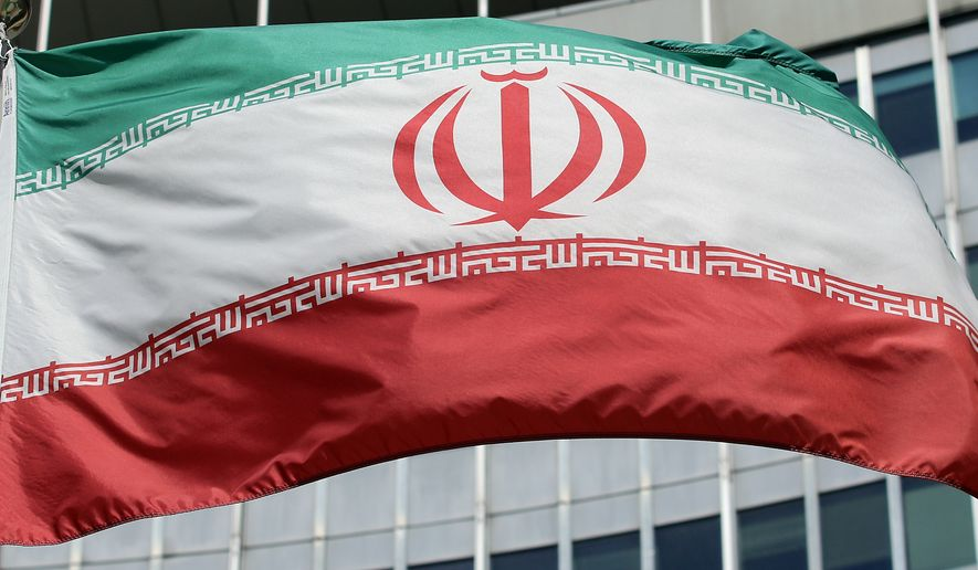 The Iranian flag flies in front of a UN building where closed-door nuclear talks take place at the International Center in Vienna, Austria, Friday, July 4, 2014. (AP Photo/Ronald Zak)