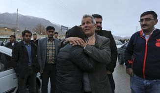 In this photo provided by Tasnim News Agency, family members of plane crash victims weep in the village of Bideh, an area near where the plane crashed, southern Iran, Sunday, Feb. 18, 2018.  An Iranian commercial plane crashed Sunday in a foggy, mountainous region of southern Iran, and officials said they feared all people aboard were killed. (Ali Khodaei,Tasnim News Agency via AP)