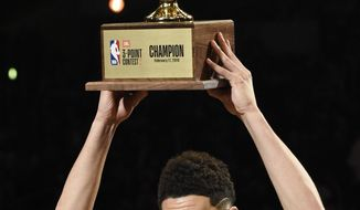 Phoenix Suns' Devin Booker holds up his trophy after winning the NBA All-Star basketball 3-Point contest, Saturday, Feb. 17, 2018, in Los Angeles. (AP Photo/Chris Pizzello)