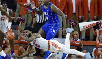 Clemson's Gabe DeVoe tries to maintain control of the ball while defended by Duke's Jordan Goldwire during the first half of an NCAA college basketball game Sunday, Feb. 18, 2018, in Clemson, S.C. (AP Photo/Richard Shiro)