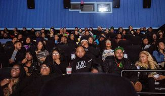 """Audience members watch the beginning of """"Black Panther"""" during a private screening on Friday, Feb. 16, 2018, in Grand Blanc, Mich.   (Bronte Wittpenn /The Flint Journal-MLive.com via AP)"""