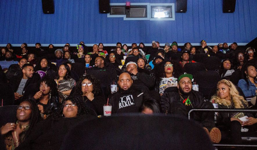 "Audience members watch the beginning of ""Black Panther"" during a private screening on Friday, Feb. 16, 2018, in Grand Blanc, Mich.   (Bronte Wittpenn /The Flint Journal-MLive.com via AP)"