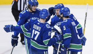 Vancouver Canucks' Loui Eriksson, of Sweden; Nic Dowd; Alex Biega; and Derrick Pouliot celebrate Eriksson's second goal against the Boston Bruins during the third period of an NHL hockey game Saturday, Feb. 17, 2018, in Vancouver, British Columbia. (Darryl Dyck/The Canadian Press via AP)