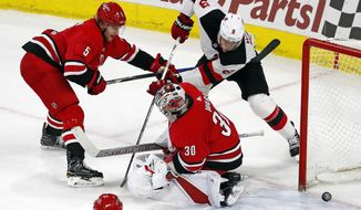 New Jersey Devils' Taylor Hall (9) forces the puck between the legs of Carolina Hurricanes goaltender Cam Ward (30) for the winning goal in overtime at an NHL hockey game Sunday, Feb. 18, 2018, in Raleigh, N.C. Hurricanes' Noah Hanifin (5) defends. (AP Photo/Karl B DeBlaker)
