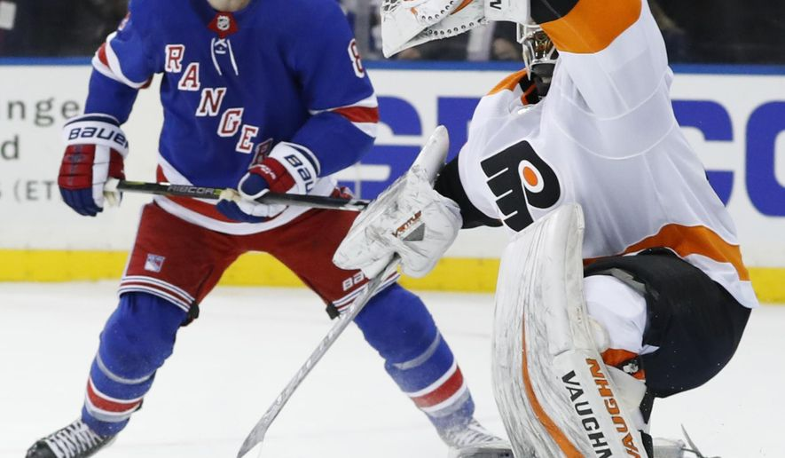 New York Rangers left wing Cody McLeod (8) watches as Philadelphia Flyers goaltender Alex Lyon (49) makes a glove save in the second period of an NHL hockey game in New York, Sunday, Feb. 18, 2018. (AP Photo/Kathy Willens)