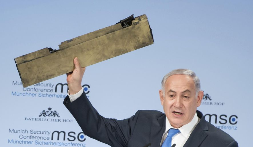 In this photo released by Lennart Preiss/MSC 2018, Israeli Prime Minister Benjamin Netanyahu, holds a part of a downed drone during his speech at the Munich Security Conference, MSC, in Munich , Germany, Sunday, Feb. 18, 2018. (Lennart Preiss/MSC 2018/dpa  via AP)