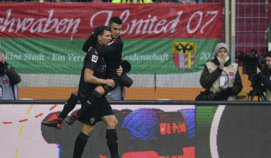 Stuttgart's Mario Gomez celebrates the opening goal  while carrying teammate Erik Thommy during the German Bundesliga soccer match between FC Augsburg and VfB Stuttgart, in Augsburg, Germany, Sunday, Feb.18, 2018. (Matthias Balk/dpa via AP)