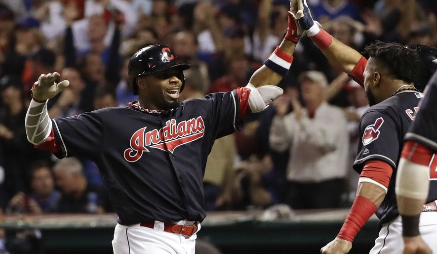 FILE - In this Nov. 2, 2016 file photo, Cleveland Indians' Rajai Davis celebrates after his two run home run against the Chicago Cubs during the eighth inning of Game 7 of the Major League Baseball World Series in Cleveland. The Indians have signed free agent Davis to a minor league contract, bringing back the speedy outfielder who hit one of the biggest home runs in team history. (AP Photo/Matt Slocum, File)