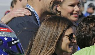 Danica Patrick, front, stands by her car with Green Bay Packers quarterback Aaron Rodgers, top, before the NASCAR Daytona 500 Cup series auto race at Daytona International Speedway in Daytona Beach, Fla., Sunday, Feb. 18, 2018. (AP Photo/Terry Renna)