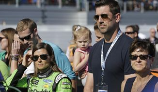Danica Patrick, left, stands with Green Bay Packers quarterback Aaron Rodgers, right, before the NASCAR Daytona 500 Cup series auto race at Daytona International Speedway in Daytona Beach, Fla., Sunday, Feb. 18, 2018. (AP Photo/Terry Renna)