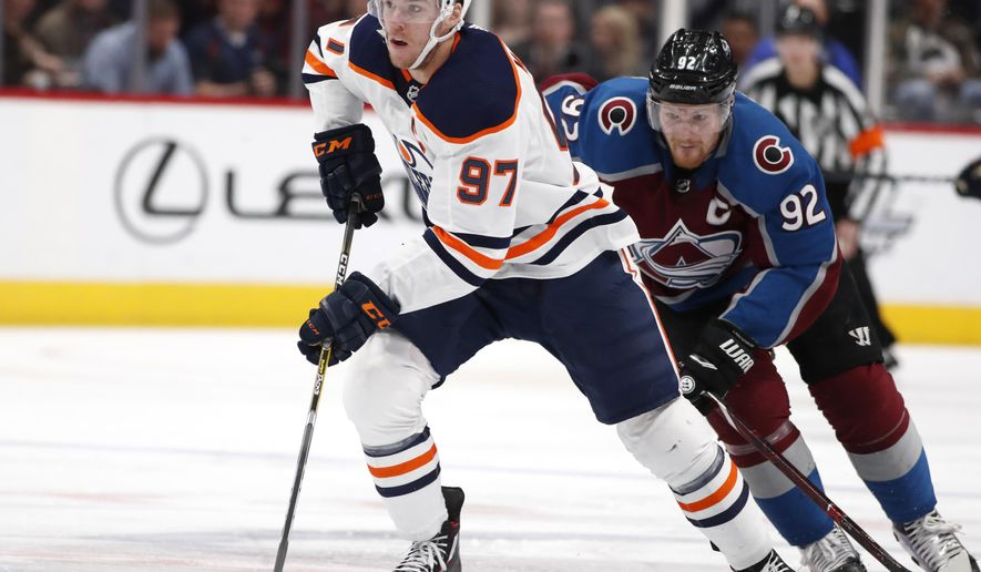 Edmonton Oilers center Connor McDavid, front, drives downice with the puck as Colorado Avalanche left wing Gabriel Landeskog pursues in the second period of an NHL hockey game Sunday, Feb. 18, 2018, in Denver. (AP Photo/David Zalubowski)