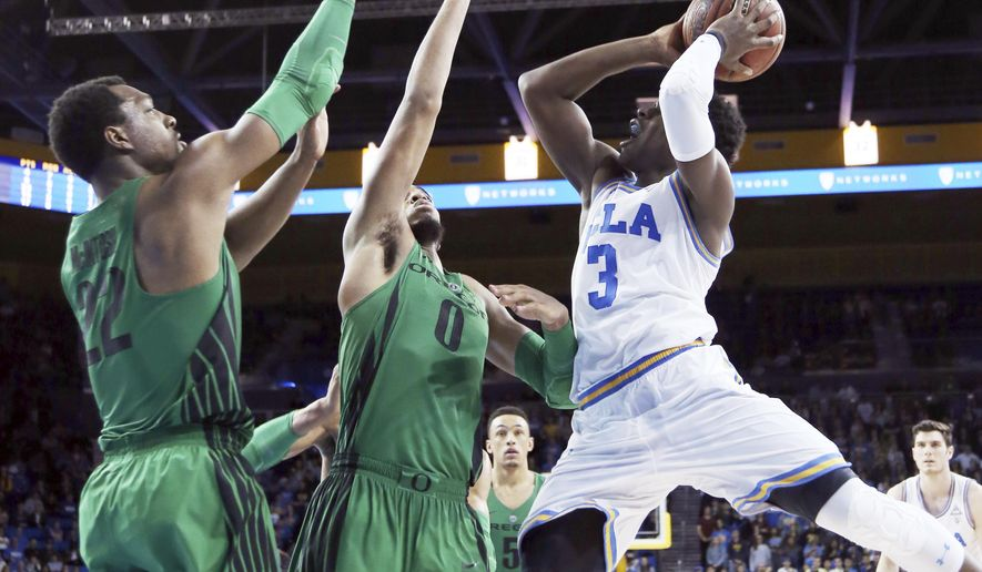 UCLA guard Aaron Holiday (3) shoots as Oregon forwards Mikyle McIntosh (22) and Troy Brown (0) defend during overtime in an NCAA college basketball game in Los Angeles Saturday, Feb. 17, 2018. UCLA won 86-78. (AP Photo/Reed Saxon)