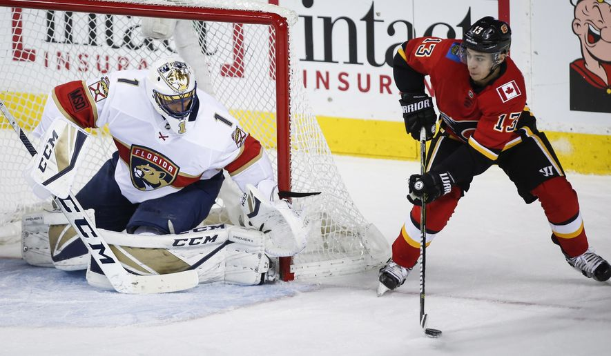 Florida Panthers goalie Roberto Luongo, left, blocks the net as Calgary Flames' Johnny Gaudreau works with the puck during the second period of an NHL hockey game Saturday, Feb. 17, 2018, in Calgary, Alberta. (Jeff McIntosh/The Canadian Press via AP)