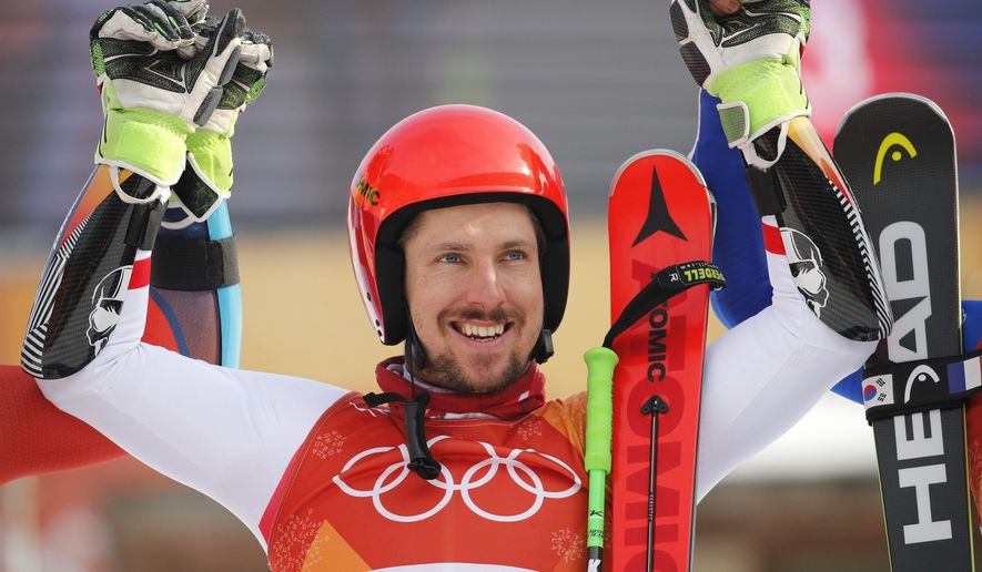 Austria's Marcel Hirscher who took the gold celebrates during the flower ceremony for the men's giant slalom at the 2018 Winter Olympics in Pyeongchang, South Korea, Sunday, Feb. 18, 2018. (AP Photo/Christophe Ena)