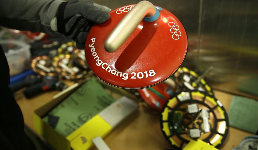 Ice technician Shawn Olesen holds a device that is placed on the curling stone at the 2018 Winter Olympics in Gangneung, South Korea, Sunday, Feb. 18, 2018. A rare hog line violation by British skip Eve Muirhead on the defending Olympic bronze medalist's last stone of the first extra end handed Sweden an 8-6 victory in the women's curling tournament on Sunday. (AP Photo/Aaron Favila)