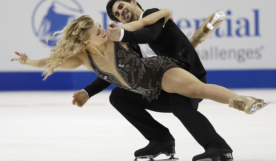 FILE - In this Jan. 7, 2018, file photo, Madison Hubbell, left, and Zachary Donohue perform during the free dance event at the U.S. Figure Skating Championships in San Jose, Calif. American ice dancer Madison Hubbell and her partner, Zachary Donohue, still rely on her mother to design and sew their costumes. (AP Photo/Tony Avelar, File)