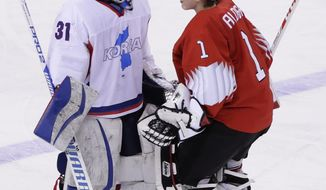 South Korea's goalie Shin So-jung (31), of the combined Koreas team, left, and goalie Janine Alder (1), of Switzerland, talk after the classification round of the women's hockey game at the 2018 Winter Olympics in Gangneung, South Korea, Sunday, Feb. 18, 2018. Switzerland won 2-0. (AP Photo/Frank Franklin II)