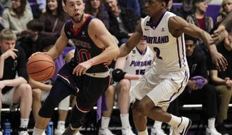 Saint Mary's guard Jordan Ford, left, drives to the basket as Portland guard JoJo Walker defends during the first half of an NCAA college basketball game in Portland, Ore., Saturday, Feb. 17, 2018. (AP Photo/Steve Dipaola)