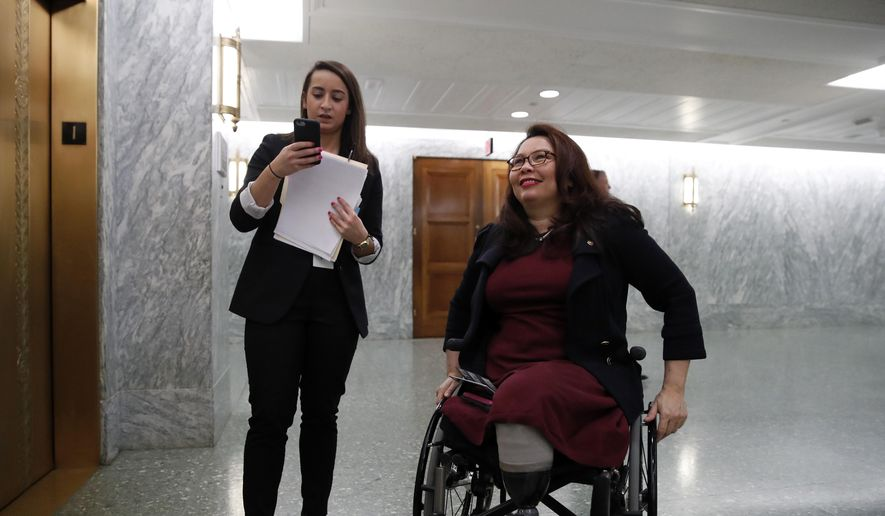 Sen. Tammy Duckworth, D-Ill., right, waits with an aide for the elevator on Capitol Hill, Wednesday, Feb. 14, 2018, in Washington. (AP Photo/Alex Brandon) ** FILE **