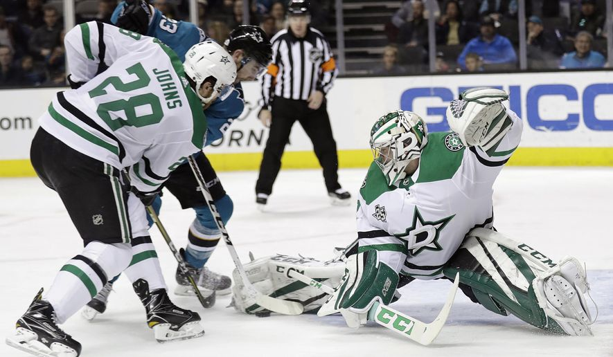 Dallas Stars goaltender Kari Lehtonen, right, stops a shot from San Jose Sharks' Barclay Goodrow, center, next to Stars' Stephen Johns (28) during the second period of an NHL hockey game Sunday, Feb. 18, 2018, in San Jose, Calif. (AP Photo/Marcio Jose Sanchez)