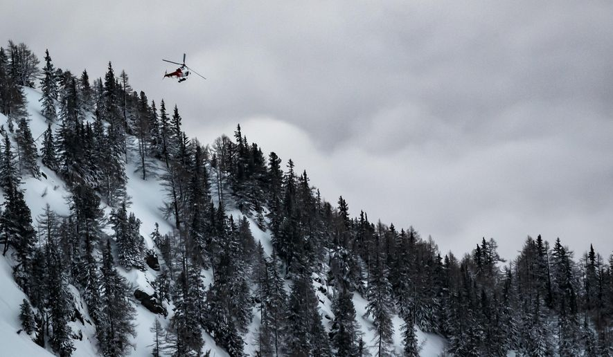 A helicopter leaves from the location where an avalanche left two people injured, at the Fenestral Pass, in Finhaut, Switzerland, Sunday, Feb. 18, 2018.  Valais police spokesman Stefan Leger said Sunday that two people were hospitalized after being pulled from the snow. (Valentin Flauraud/Keystone via AP)