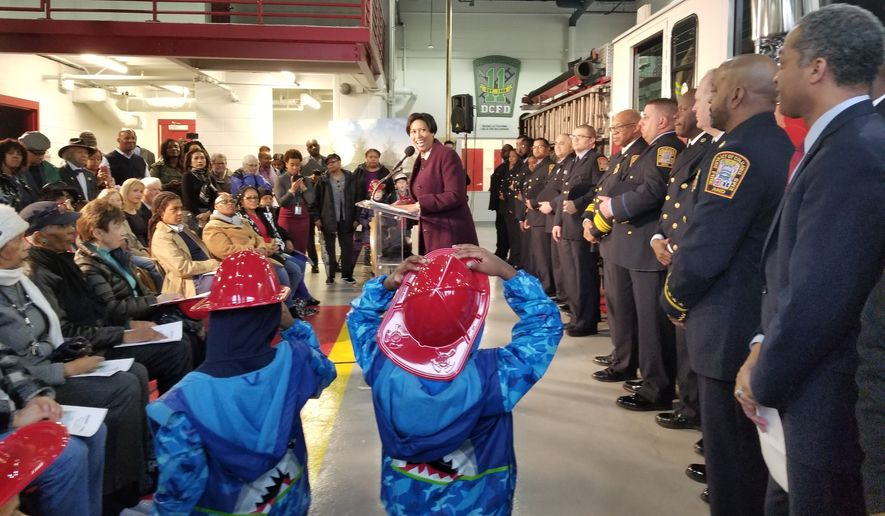 Twin brothers Zephaniah Chamber, 6, and Dylan Chambers, 6, hold onto their hats as they watch Mayor Muriel Bowser announce the opening of the new Engine Company 22 firehouse on upper Georgia Avenue to a crowd of Ward 4 neighbors. The ribbon cutting ceremony on February the 16th, 2018 marks 121 years since Brightwood Park updated its original chemical firehouse which employs 12 fireman who operate a fire truck, a fire engine, and an ambulance. (Julia Airey/The Washington Times)
