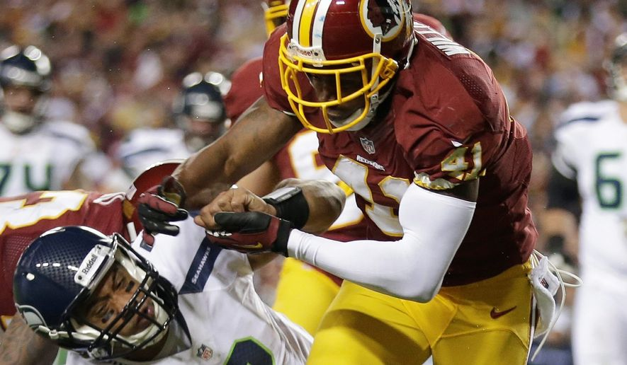 Washington Redskins free safety Madieu Williams stops Seattle Seahawks quarterback Russell Wilson during the first half of an NFL wild card playoff football game in Landover, Md., Sunday, Jan. 6, 2013. (AP Photo/Evan Vucci)