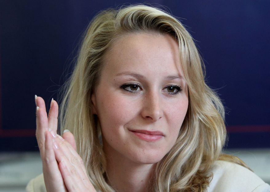 Far-right National Front party regional leader for southeastern France Marion Marechal-Le Pen attends a press conference in Bayonne, southwestern France, Tuesday, April 11, 2017. She is campaigning for far-right candidate for the presidential election Marine Le Pen, seen on poster behind. The top two vote-getters on April 23 will compete in a presidential runoff on May 7. (AP Photo/Bob Edme)
