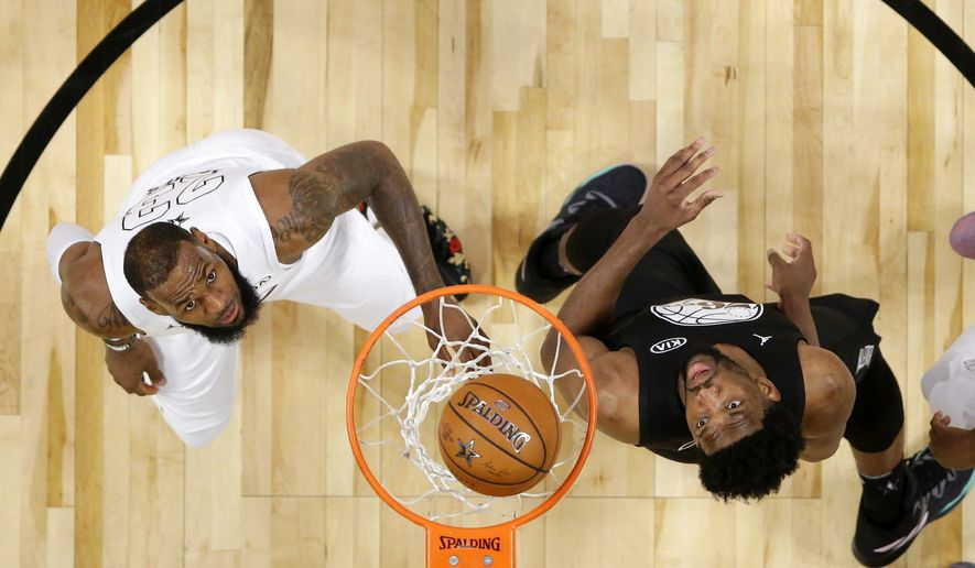Team LeBron's LeBron James, left, of the Cleveland Cavaliers, and Team Stephen's Joel Embiid, of the Philadelphia 76ers, wait for a rebound during the second half of an NBA All-Star basketball game, Sunday, Feb. 18, 2018, in Los Angeles. (Mike Nelson/Pool via AP)