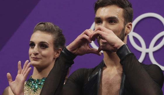Gabriella Papadakis and Guillaume Cizeron of France react as their points are posted following their performance in the ice dance, short dance figure skating in the Gangneung Ice Arena at the 2018 Winter Olympics in Gangneung, South Korea, Monday, Feb. 19, 2018. (AP Photo/Julie Jacobson)