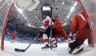 Russian athlete Liana Ganeyeva (11) checks Haley Irwin (21), of Canada, as Russian athlete Valeria Tarakanova (1) handles the puck during the first period of the semifinal round of the women's hockey game at the 2018 Winter Olympics in Gangneung, South Korea, Monday, Feb. 19, 2018. (Matt Slocum/Pool Photo via AP)