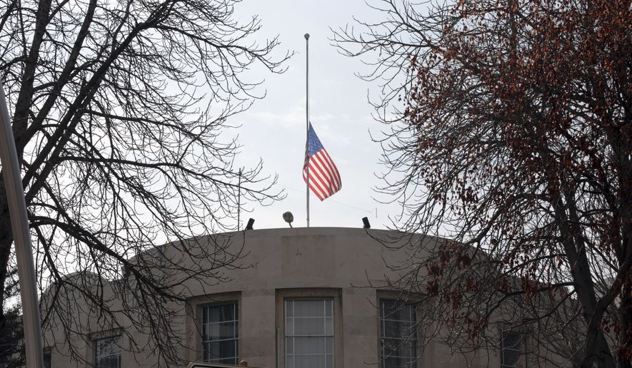"""The U.S. Embassy's flag flies at half-mast in respect for the Florida school shooting victims in Ankara, Turkey, Monday, Feb. 19, 2018. Municipality workers on Monday took down the street sign for Nevzat Tandogan Street where the U.S. Embassy is located and replaced it with one that reads """"Olive Branch Street."""" (AP Photo/Burhan Ozbilici)"""