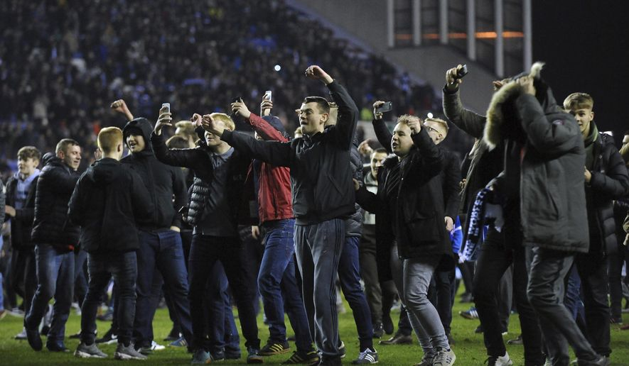 Wigan Athletic fans celebrate at the end of the English FA Cup fifth round soccer match between Wigan Athletic and Manchester City at The DW Stadium, Wigan, England, Monday, Feb. 19, 2018. Wigan Athletic won the game 1-0. (AP Photo/Rui Vieira)