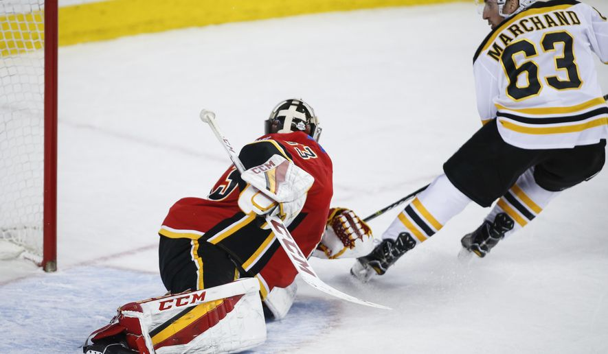 Boston Bruins' Brad Marchand, right, scores the game-winning goal on Calgary Flames goalie David Rittich, from the Czech Republic, during overtime NHL hockey action in Calgary, Monday, Feb. 19, 2018. (Jeff McIntosh/The Canadian Press via AP)