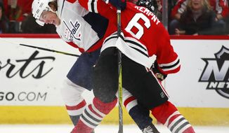 Washington Capitals right wing T.J. Oshie (77) battles Chicago Blackhawks defenseman Michal Kempny (6) for the puck during the first period of an NHL hockey game Saturday, Feb. 17, 2018, in Chicago. (AP Photo/Jeff Haynes)