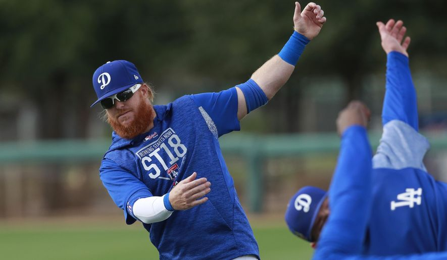 Los Angeles Dodgers third baseman Justin Turner stretches with teammates at the team's spring training baseball facility Monday, Feb. 19, 2018, in Glendale, Ariz. (AP Photo/Carlos Osorio)