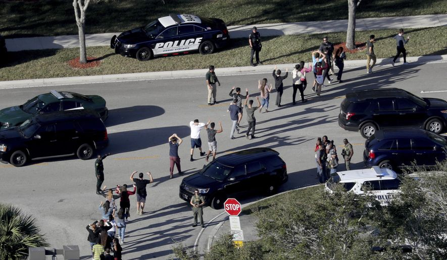 In a Wednesday, Feb. 14, 2018, file photo, students hold their hands in the air as they are evacuated by police from Marjory Stoneman Douglas High School in Parkland, Fla., after a shooter opened fire on the campus. (Mike Stocker/South Florida Sun-Sentinel via AP, File)