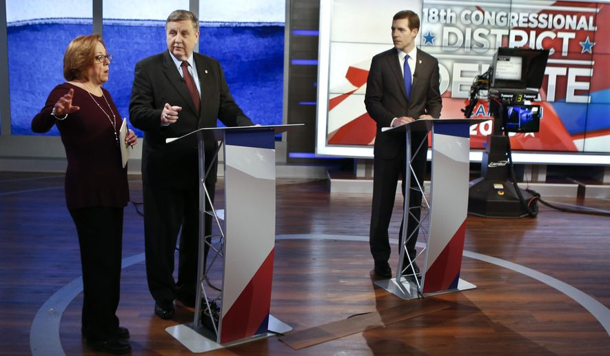 Republican Rick Saccone, center, and Democrat Connor Lamb, right, are prepped for the taping of their first debate in the special election in the Pa., 18th Congressional District at the KDKA TV studios, Monday, Feb. 19, 2018, in Pittsburgh. The debate was recorded in the afternoon and scheduled to be broadcast at 7 PM Monday. (AP Photo/Keith Srakocic)