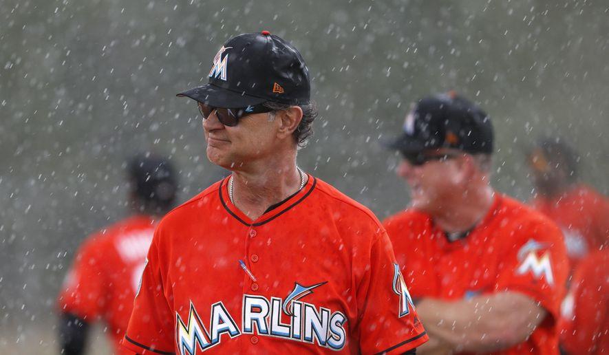 Miami Marlins manager Don Mattingly walks through a steady rain during spring training baseball practice Monday, Feb. 19, 2018, in Jupiter, Fla. (AP Photo/Jeff Roberson)