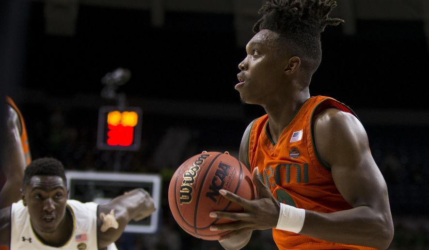 Miami's Lonnie Walker IV, right, sets up for a shot in front of Notre Dame's T.J. Gibbs (10) during the first half of an NCAA college basketball game Monday, Feb. 19, 2018, in South Bend, Ind. Miami won 77-74. (AP Photo/Robert Franklin)