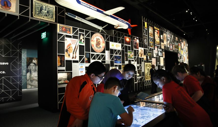 "A school groups explores an interactive touch table to learn about the objects and images on display at the ""Americans"" exhibit at the Smithsonian's National Museum of the American Indian, Friday, Feb. 9, 2018, in Washington. The exhibit uses Native imagery to show how it permeates American culture. (AP Photo/Jacquelyn Martin)"
