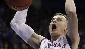 Kansas forward Mitch Lightfoot (44) dunks during the first half of an NCAA college basketball game against Oklahoma in Lawrence, Kan., Monday, Feb. 19, 2018. (AP Photo/Orlin Wagner)