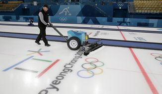 In this Sunday, Feb. 18, 2018 photo, Shawn Oleson, an assistant ice technician for the U.S. Curling Association, works on the ice at the curling center in Gangneung, South Korea. Curling is the busiest sport at the Olympics, with 18 straight days of competition and as many as three sessions with four concurrent matches per day. And between each game, the ice needs to be repaired and prepared with a new layer of pebbles, which reduce the friction on the 42-pound curling stones as they slide down the ice on the bending route that gives the sport its name.  (AP Photo/Aaron Favila)