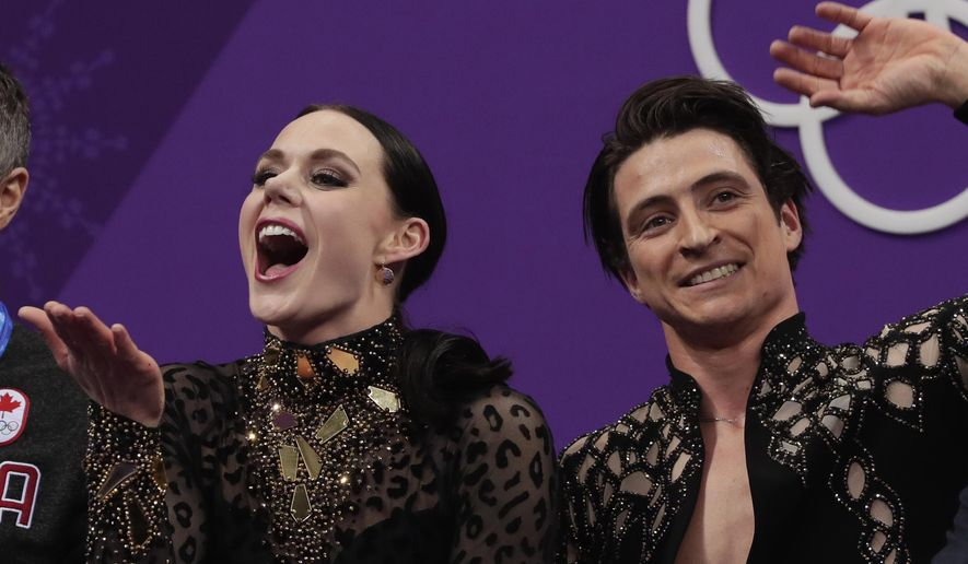 Tessa Virtue and Scott Moir of Canada react as their points are posted following their performance in the ice dance, short dance figure skating in the Gangneung Ice Arena at the 2018 Winter Olympics in Gangneung, South Korea, Monday, Feb. 19, 2018. (AP Photo/Julie Jacobson)