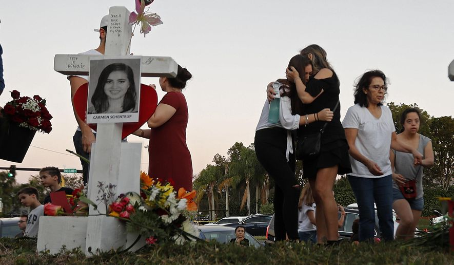 Magaly Newcomb, right comforts her daughter Haley Newcomb, 14, a student at Marjory Stoneman Douglas High School, at a makeshift memorial outside the school, in Parkland, Fla., Sunday, Feb. 18, 2018.  Nikolas Cruz, a 19-year-old who had been expelled from the school, is being held without bail in the Broward County Jail, accused of 17 counts of first-degree murder.  (AP Photo/Gerald Herbert)