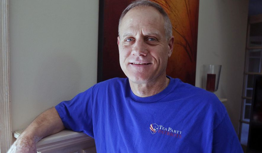 In this Feb. 16, 2018, photo, Andy Cilek poses with a Tea Party shirt at his home in Eden Prairie, Minn. Cilek was one of two voters who defied elections officials after he was asked to cover up a tea-party shirt and button. A Minnesota law that bars voters from wearing political hats, T-shirts, buttons and other apparel to the polls is about to get a look from the Supreme Court. (AP Photo/Jim Mone)