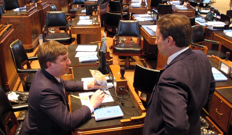 Rep. Jean-Paul Coussan, R-Lafayette, left, speaks with Rep. Tanner Magee, R-Houma, on the opening day of the special legislative session on Monday, Feb. 19, 2018, in Baton Rouge, La. (AP Photo/Melinda Deslatte)