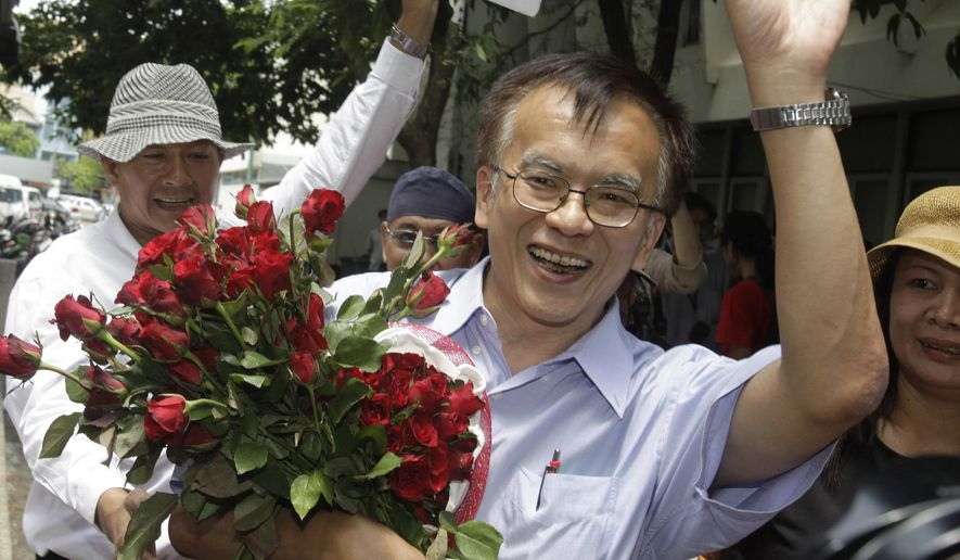 FILE - In this May 11, 2011 file photo, historian Somsak Jeamteerasakul holds flowers from his supporters as he walks out of a police station, where police heard about an article he wrote about a Thai royal family member, in Bangkok, Thailand. A Thai legal aid group said Monday, Feb. 19, 2018,  that a caricature of historian Somsak Jeamteerasakul, a critic in exile of Thailand's monarchy, was auctioned online  for $6,400 to be used to bail out political prisoners.  (AP Photo/Sakchai Lalit, File)