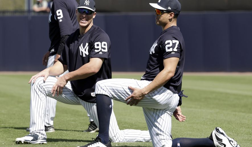 New York Yankees' Aaron Judge (99) and Giancarlo Stanton 927) stretch at baseball spring training camp, Monday, Feb. 19, 2018, in Tampa, Fla. (AP Photo/Lynne Sladky)